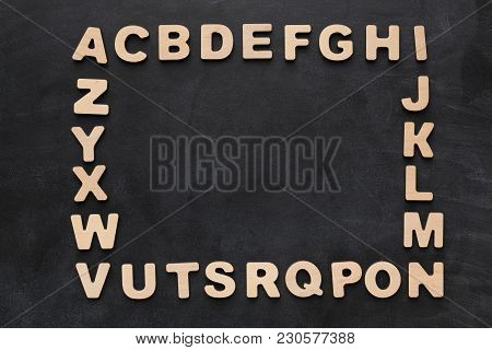 English Letters On Black Background, Copy Space. Wooden Aphabet Arranged By Order In Rectangle Frame