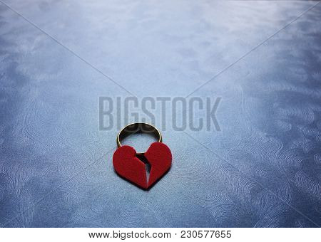 Broken Red Heart And Wedding Ring On Blue