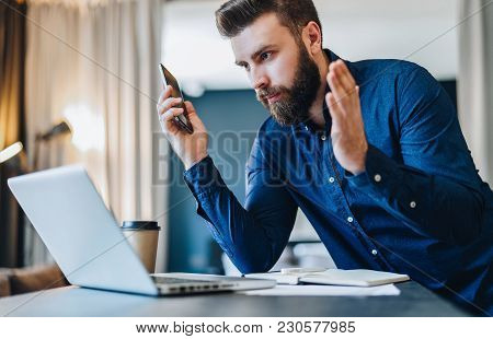 Young Bearded Businessman Sits In Front Of Computer And Looks At Laptop Screen With Astonishment, Ra