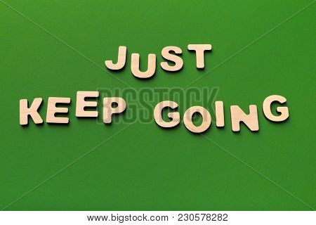 Motivation Poster. Phrase Just Keep Going Spelled With Wooden Letters On Green Background. Motivatio