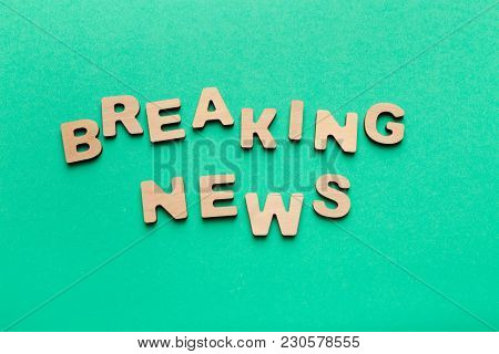 Breaking News Phrase Spelled With Wooden Letters On Green Background. Broadcasting, Announcement And