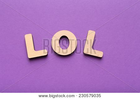 Word Lol Spelled Out With Wooden Letters On Violet Background. Abbreviation Stands For Laugh Out Lou