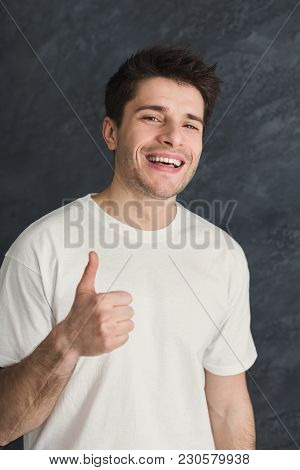 Young Smiling Man With Thumb Up Portrait. Cheerful Guy Gesturing That All Is Great, Gray Studio Back