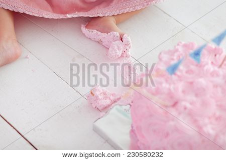 Dirty Baby Feet On White Wooden Floor Background, First Birthday Cake Smash.