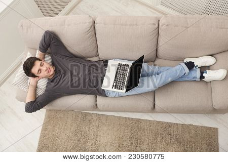 Tired Guy Having Rest, Overworked Man Freelancer With Laptop Dreaming On Couch At Home, Top View, Co