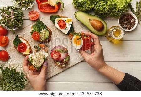 Female Hands Holding Bruschettas With Cheese, Egg, Microgreen And Tomato. Healthy Vegetarian Sandwic