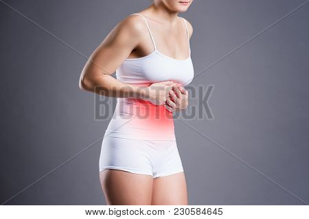 Woman With Abdominal Pain, Stomachache On Gray Background, Studio Shot