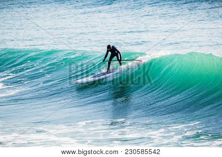 Surfer In Wet Suit On Stand Up Paddle Board On Ocean Waves. Stand Up Paddle Boarding In Sea