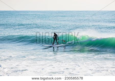 Surfer On Stand Up Paddle Board On Ocean Waves. Stand Up Paddle Boarding In Sea