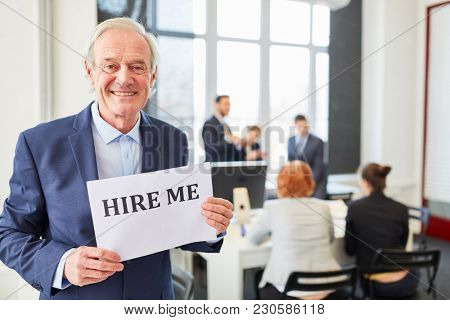 Senior businessman looking for a job holds sign that reads