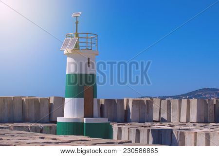 Green Stripped Light House Surrounded By Sea Breakers