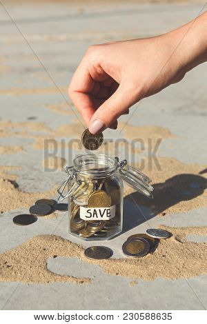 Hand Putting Coins In Glass Jar With Save Label On Gray Background. Money Saving For House, Dream, V
