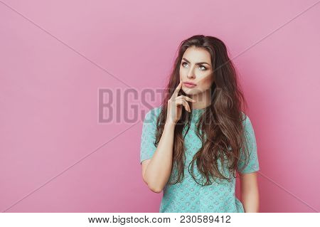 Portrait Of Attractive Thoughtful Young Female Holding Forefinger Up Looking Away With Sly Smile. Pr