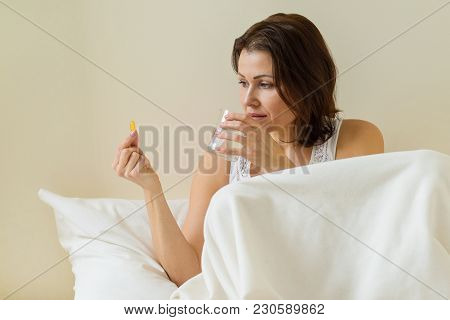 Woman Takes Pill With Omega-3 And Holding A Glass Of Fresh Water In Bed Morning. Vitamin D, E, A Fis