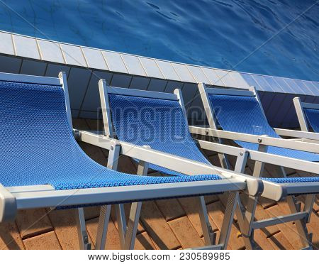 Blue Loungers Lined Up On The Edge Of A Swimming Pool In A Tourist Village
