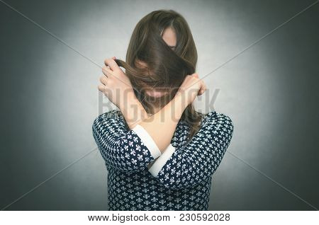 Offended Woman Hides Her Face Behind Her Hairs Isolated On Gray Background. Incognito. Faceless Pers
