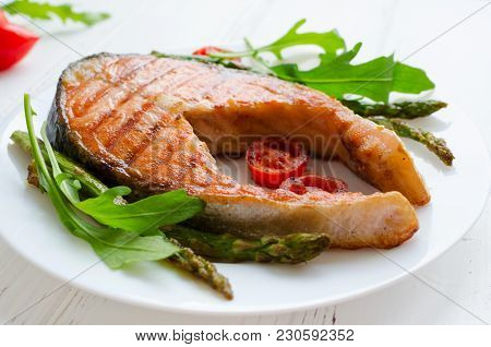 Grilled Salmon Steak With Asparagus, Tomatoes Cherry And Arugula On A Plate On White Wooden Backgrou