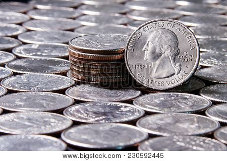Blurry Dice Rolled Over Silver Us Currency Quarters In A Uniform Pattern 1