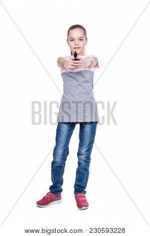 Young Girl In A T-shirt And Jeans With A Smile On Her Face Aiming A Gun In The Camera Isolated On A