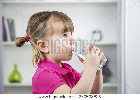 Child Drinks Water From A Glass Of Glass At Home. Health And Beauty Concept