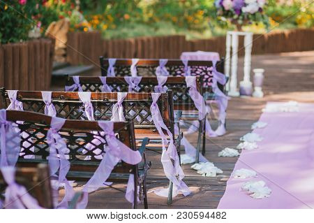 Wooden Benches In The Wedding Ceremony Area In The Garden, Decorated With Purple Ribbons. Horizontal