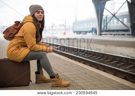 Woman Wait For Train On Railway Station. Travel Concept. Surfing Internet On Phone To Kill Time