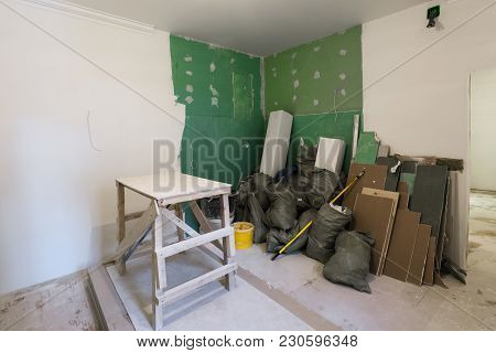 Wooden Board In Room, Sheets Of Plasterboard Or Drywall And Construction Garbage In The Bags Are An