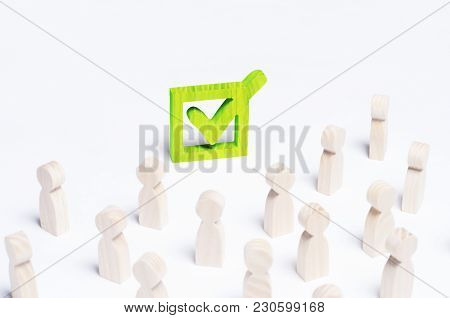 A Crowd Of People Looks At The Green Tick In The Box. The Concept Of The Political Process And Democ
