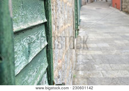 Part Of Wooden Blinds With An Alley Paved With Stones