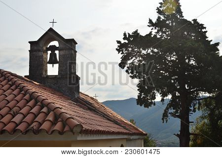 Belfry On A Roof Of A Small Church With A Tree Top Beside