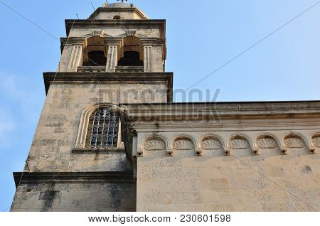 High Belfry And Part Of A Church Building Against Blue Sky