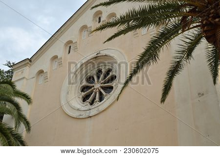 Front Wall Of An Ancient Monastery With Palm Branches