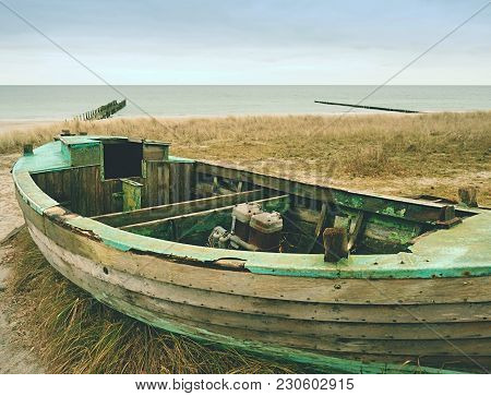 Wrecked Fishing Boat On Old Dry Grass. Abandoned Wooden Ship With Damaged Engine Stay On Sandy Dune