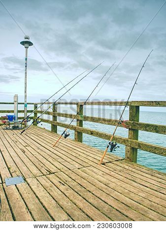 Several Fishing Rods Against The Wooden Railing Of The Beach Pier. Overcast Day, With The Hidden Sun