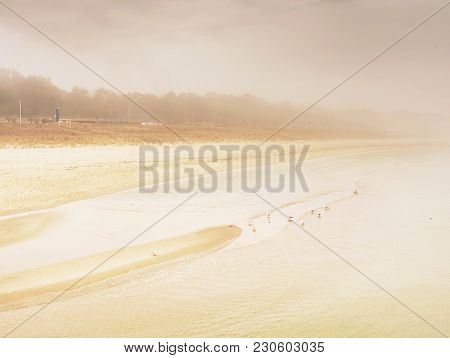 Island Coastline Within Misty Morning. Landscape With Sandy Beach And Sea Level Ending In Clouds. Wa