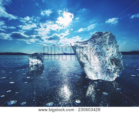 Beautiful Transparent Piece Ice Of Lake Against Dark Blue Sky And  Bright Sun.