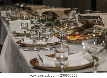 Served Table In Restaurant, Glasses And Dishes With Meat And Fruit For A Holiday