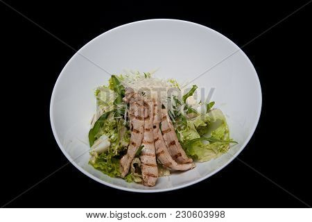Close-up Of Tasty Fresh Caesar Salad With Chicken And Vegetables Decorated With Balsamic Sauce On Wh