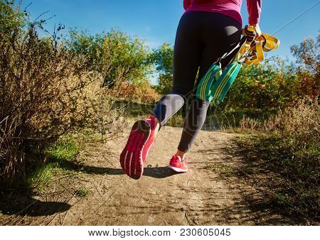 Closeup Of Sportswoman With Suspension Straps Walking On Autumn Road