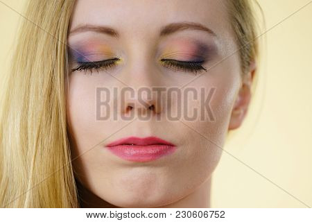 Young Woman Having Serious Face Expression And Beautiful Colorful Makeup, Eyes Closed. Visage Beauty