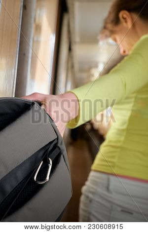 Closeup Of Female Hand Taking Out Her Backpack From Compartment In Train