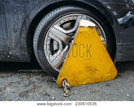 Yellow Triangle Wheel Clamp Locked With Messing Lock And Chain On An Illegally Parked Car