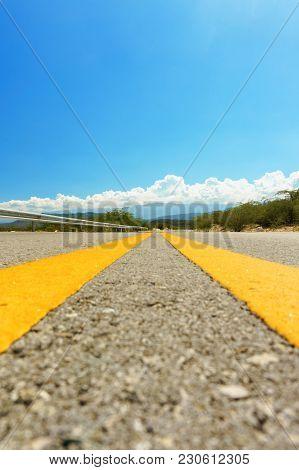 Yellow Dividing Line On Asphalt Road On Blue Sky Background