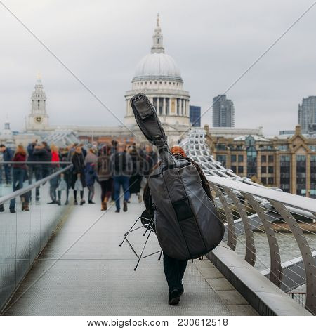 Back Of Unidentifitable Musical Street Performer Carrying An Upside Down Cello On The Millenium Brid