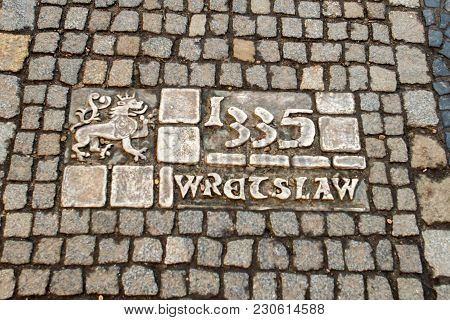 Wroclaw, Poland - March 9, 2018: One Of The Metal Plaques On Wroclaw's Sidewalk Timeline Commemorati