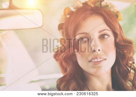 Closeup authentic portrait of a nice redhead female with freckles wearing floral wreath, natural beauty of Slavonian women, photo with bright sun flare