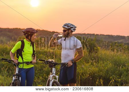 Cyclists Man And Woman Stopped To Drink Water On The Journey.