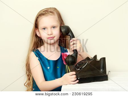 Beautiful Little Girl With Long Blond Hair, Holds The Ear Of An Old Apartment Phone.
