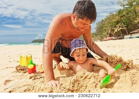 Boy and dad playing in the sand on the beach