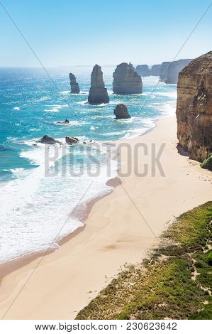 Twelve Apostels With Beach And Grass And Backlight At The Great Ocean Road Vertical, Victoria, Austr